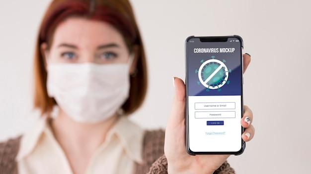 Vrouw die met maskers smartphone houdt Gratis Psd