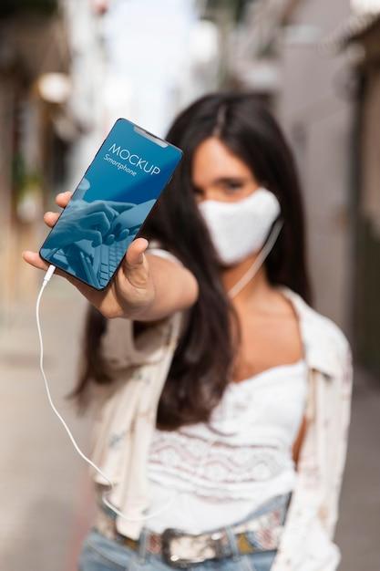 Vrouw die met medisch masker aan muziek op oortelefoons luistert Gratis Psd