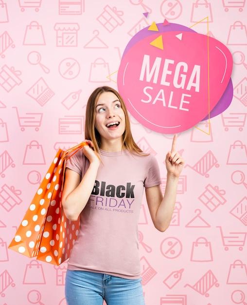 Vrouw die papieren zakken houdt en een zwart vrijdag-t-shirt draagt Gratis Psd