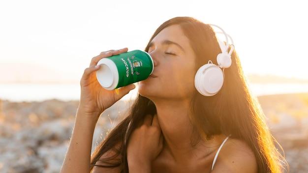 Vrouw drinken uit frisdrankblikje en luisteren naar muziek op de koptelefoon Gratis Psd