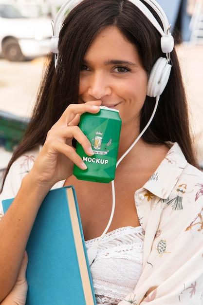 Vrouw frisdrank drinken en luisteren naar muziek terwijl ze boek vasthoudt Gratis Psd
