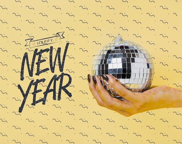 Vrouw met discobal met nieuwjaar belettering Gratis Psd