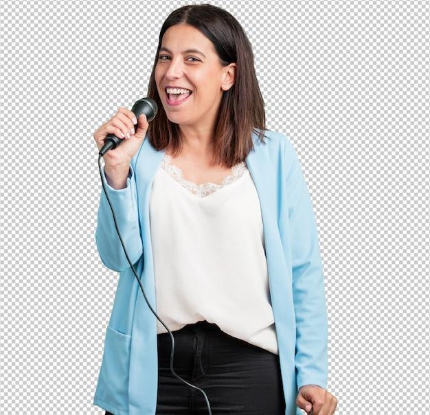 Vrouw van middelbare leeftijd gelukkig en gemotiveerd, zing een lied met een microfoon, presenteer een evenement of heb een feest, geniet van het moment Premium Psd