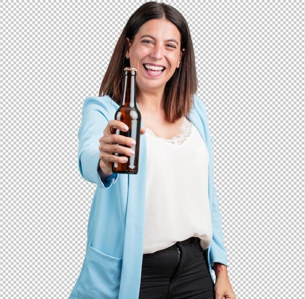 Vrouw van middelbare leeftijd gelukkig en leuk, met een flesje bier, voelt goed na een intensieve werkdag, klaar om een voetbalwedstrijd op televisie te kijken Premium Psd