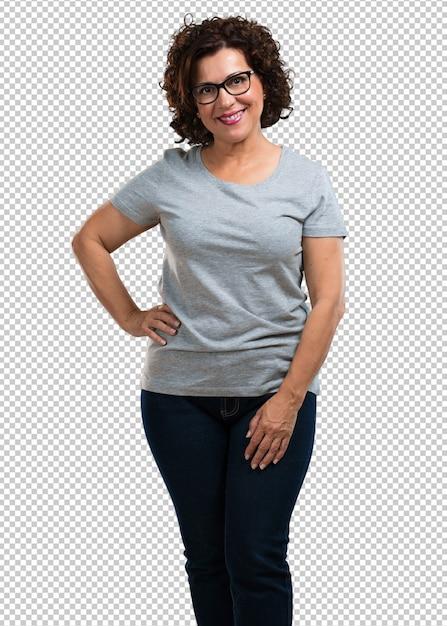 Vrouw van middelbare leeftijd met handen op de heupen, permanent, ontspannen en glimlachend, zeer positief en vrolijk Premium Psd
