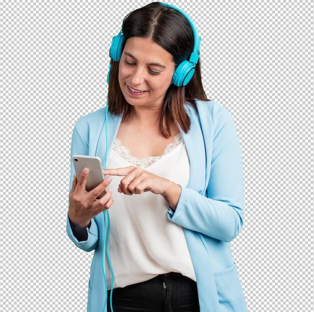 Vrouw van middelbare leeftijd ontspannen en geconcentreerd, luisteren naar muziek met zijn mobiele telefoon Premium Psd