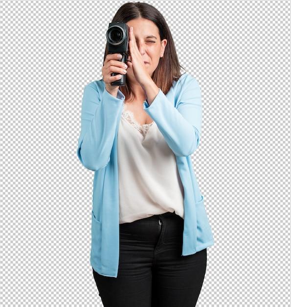 Vrouw van middelbare leeftijd opgewonden en vermaakt, kijkend door een filmcamera, op zoek naar een interessant schot, een film opnemen, uitvoerend producent Premium Psd