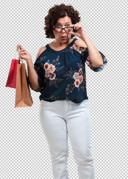 Vrouw van middelbare leeftijd vrolijk en glimlachend, erg opgewonden met een boodschappentas, klaar om te gaan winkelen en op zoek te gaan naar nieuwe aanbiedingen Premium Psd