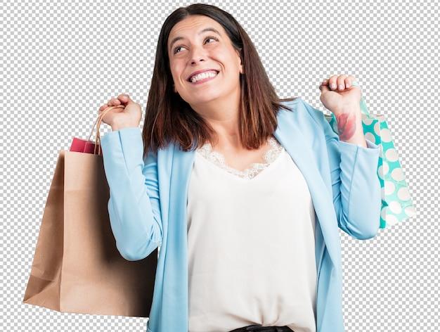 Vrouw van middelbare leeftijd, vrolijk en lachend, zeer enthousiast met een boodschappentas Premium Psd