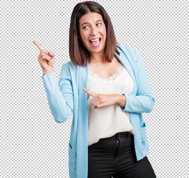 Vrouw van middelbare leeftijd wijst naar de kant, glimlachend verrast presenteren iets, natuurlijk en casual Premium Psd