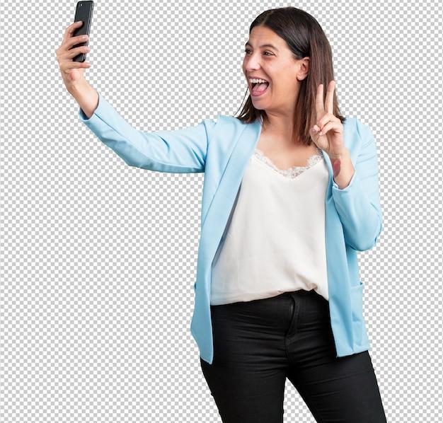 Vrouw van middelbare leeftijd zelfverzekerd en opgewekt, een selfie maken, naar de mobiel kijken met een grappig en zorgeloos gebaar, surfen op de sociale netwerken en internet Premium Psd