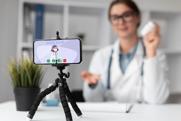 Vrouwelijke arts met een mock-up smartphone Premium Psd