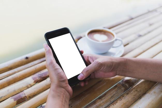 Vrouwen die een smartphonemodel op een bamboelijst houden Premium Psd
