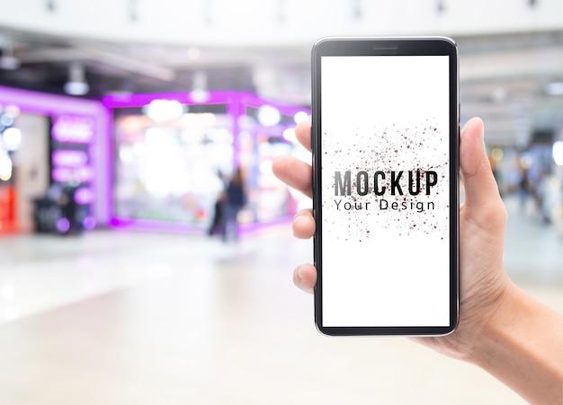 Vrouwenhand die en zwarte smartphone met leeg het schermmodel houden voor uw ontwerp op abstract onduidelijk beeldwarenhuis of winkelcomplex. Premium Psd