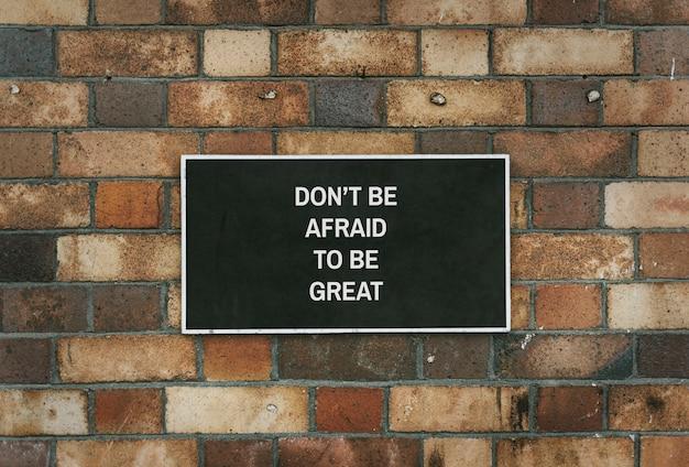 Wees niet bang om een geweldig bordmodel te zijn op een bakstenen muur Gratis Psd