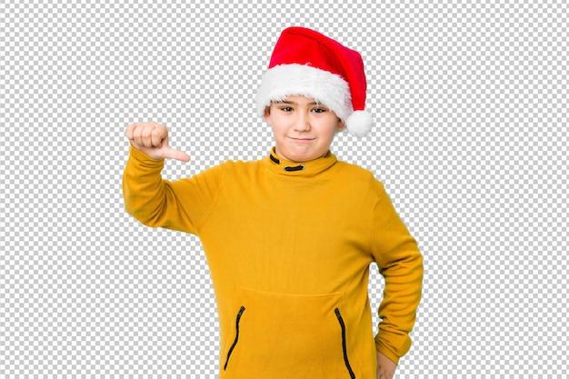 Weinig jongen het vieren kerstmisdag die een santahoed draagt die een afkeergebaar tonen, duimen neer. meningsverschil concept. Premium Psd