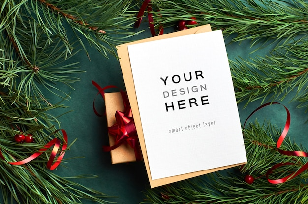 Wenskaart mockup met kerst geschenkdoos en pijnboomtakken met bureaucratie op groen Premium Psd