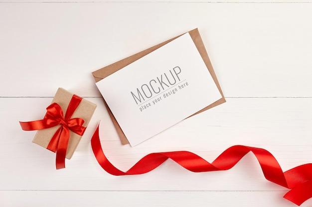 Wenskaartmodel met geschenkdoos en rood lint Premium Psd