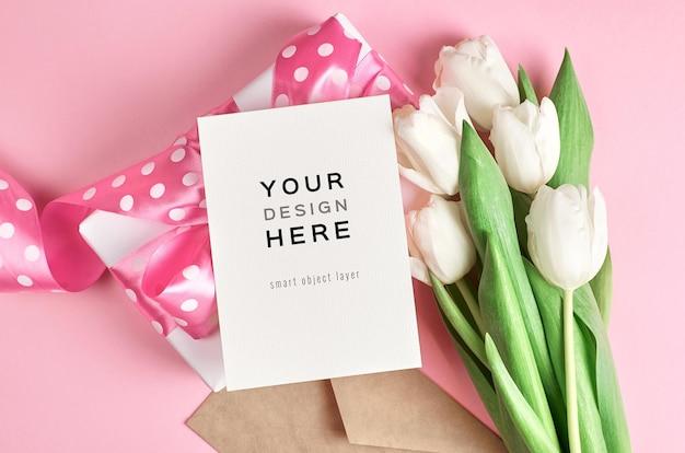 Wenskaartmodel met geschenkdoos en wit tulp bloemenboeket op roze Premium Psd