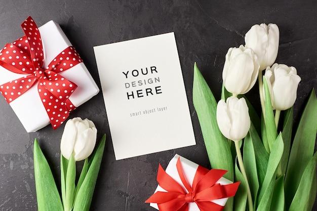 Wenskaartmodel met geschenkdoos en witte tulp bloemen op zwart Premium Psd