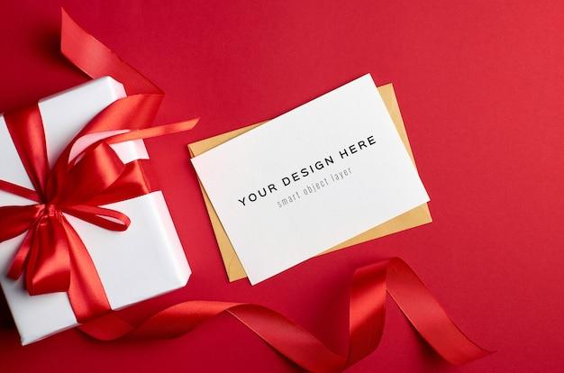 Wenskaartmodel met geschenkdoos op rode achtergrond Premium Psd