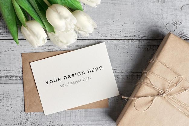 Wenskaartmodel met tulp bloemen en geschenkdoos op houten achtergrond Premium Psd