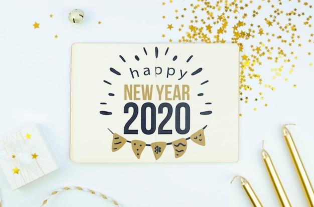 Witte kaart met gelukkig nieuwjaar 2020-citaat en gouden accessoires Gratis Psd
