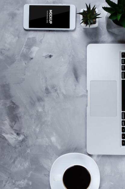 Witte smartphone met zwart leeg scherm op bureau met laptop en kopje koffie Premium Psd