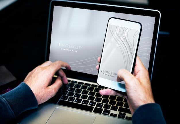 Zakenman die laptop en een mobiel telefoonmodel met behulp van Gratis Psd