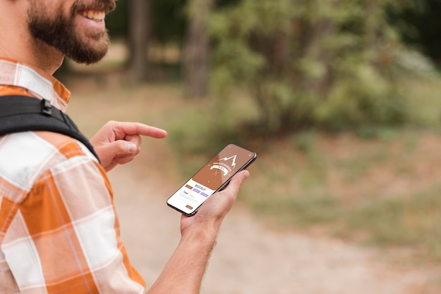 Zijaanzicht van smiley man met smartphone tijdens het kamperen Gratis Psd