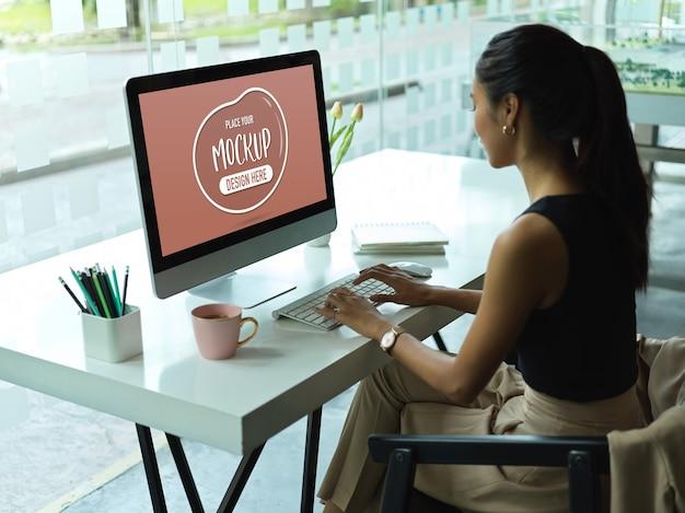 Zijaanzicht van vrouwelijke beambte die op mockupcomputer werkt Premium Psd