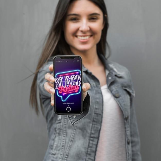 Zwart vrijdagmodel met smartphone van de vrouwenholding Gratis Psd