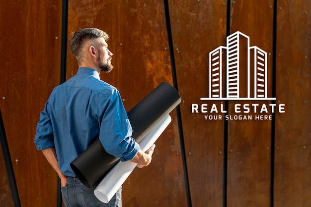 Agent homme tenant des plans pour le nouveau bâtiment par derrière Psd gratuit