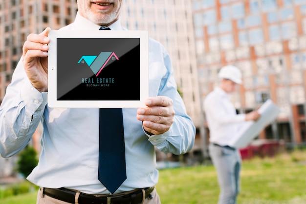 Architecte tenant une tablette maquette devant un bâtiment Psd gratuit