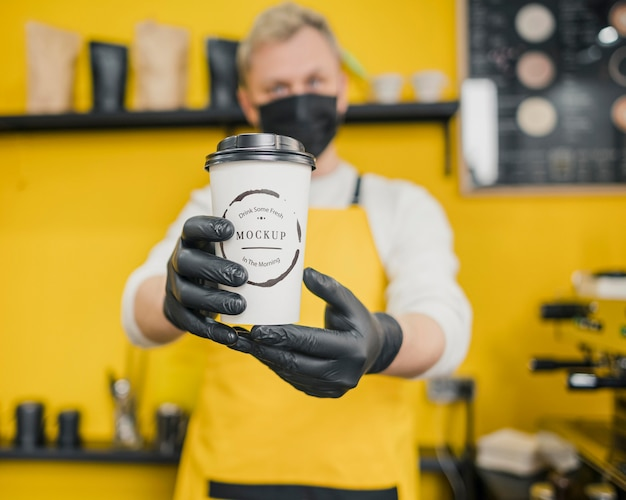 Barista Tenant Une Maquette De Tasse à Café Psd gratuit