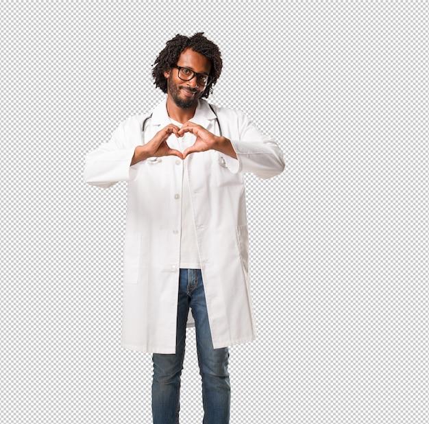 Beau docteur afro-américain faisant un coeur avec les mains, exprimant l'amour et l'amitié, heureux et souriant PSD Premium