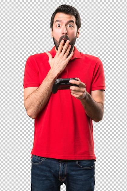 Beau jeune homme jouant à des jeux vidéo et faisant un geste de surprise PSD Premium