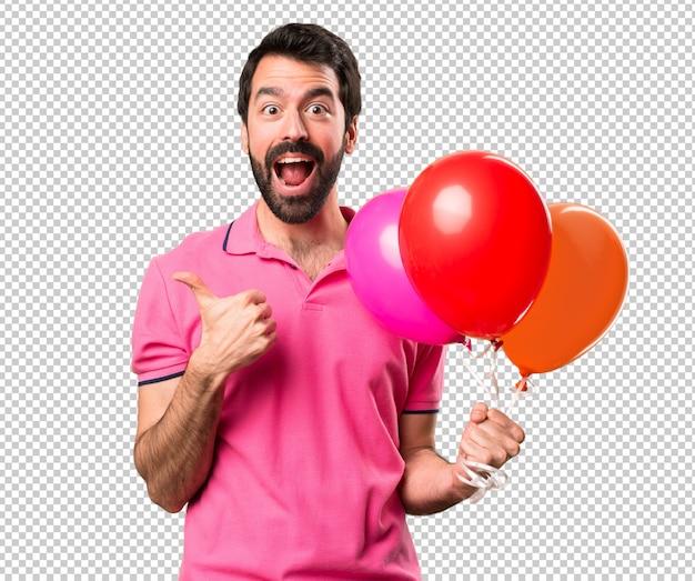 Beau jeune homme tenant des ballons et avec le pouce PSD Premium