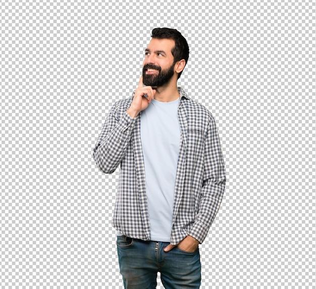 Bel homme à la barbe pense à une idée tout en levant les yeux PSD Premium