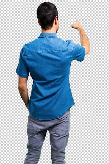 Bel homme avec une chemise bleue pointant en arrière avec l'index PSD Premium