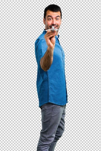 Bel homme avec une chemise bleue tenant un avion jouet PSD Premium