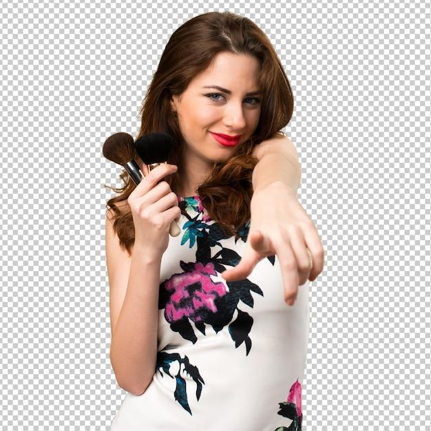 Belle jeune fille avec un pinceau de maquillage pointant vers l'avant PSD Premium