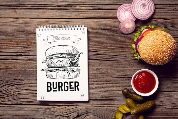 Bloc-notes Avec Croquis De Burger Sur Fond En Bois Psd gratuit