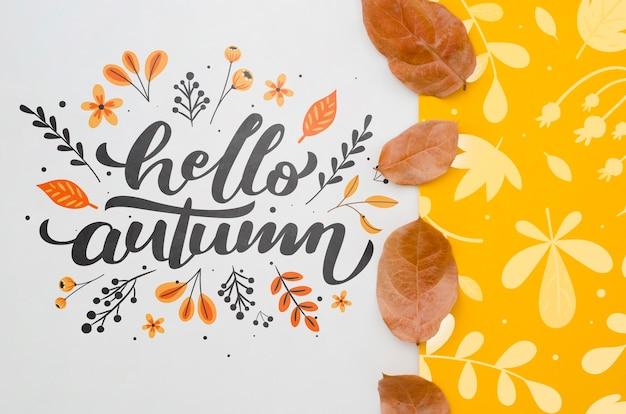 Bonjour lettrage d'automne à côté de motif de feuilles jaunes Psd gratuit
