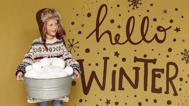 Bonjour texte d'hiver et garçon avec un seau plein de boules de neige Psd gratuit