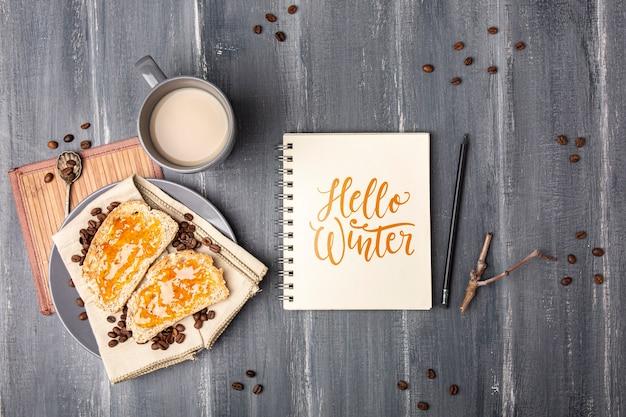 Cahier avec bonjour message d'hiver à côté du petit déjeuner Psd gratuit