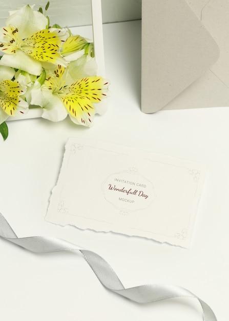 Carte d'invitation sur fond blanc, bouquet de fleurs et enveloppe grise PSD Premium
