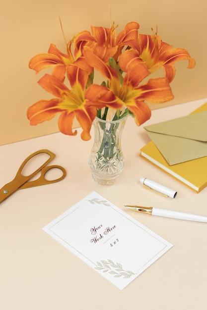 Carte d'invitation maquette avec des fleurs orange, des notes et des ciseaux d'or PSD Premium