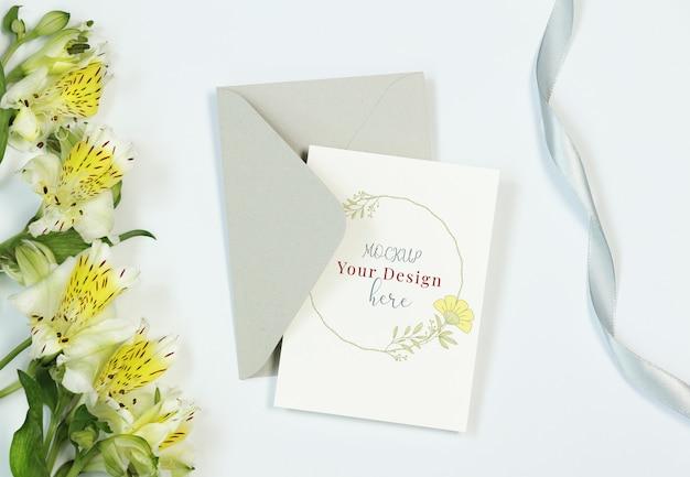 Carte d'invitation de maquette sur fond blanc avec fleurs, enveloppe et ruban PSD Premium
