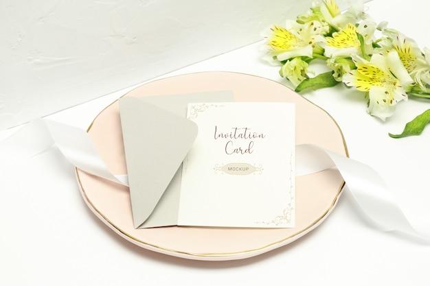 Carte postale sur une assiette rose avec ruban blanc, enveloppe grise et fleurs blanches PSD Premium